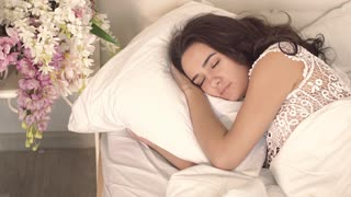 Close-up of happy young woman getting coffee in bed from her caring husband