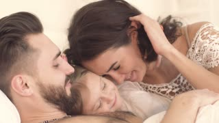 Close-up of lovely tender family lying in bed together