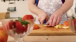 Close-up of the hand of a man and woman who prepare a fruit salad with strawberries.