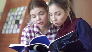 Close-up of two focused college girls discussing articles in library magazines