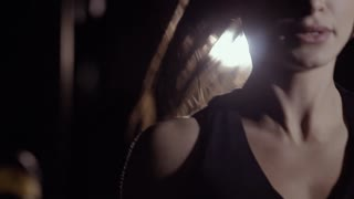Close-up of woman doing rope jumping against artificial light background.