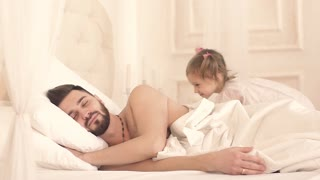 Cute little girl waking her father up and hugging