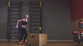 Female athletes doing box jumps at gym
