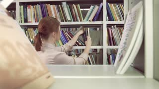 Female student among bookcases in library looking for books