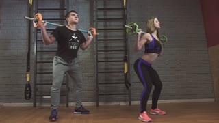 Fitness couple exercising in gym with barbell weights