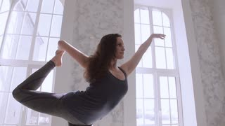 Flexible girl in blue clothes doing yoga asanas at room