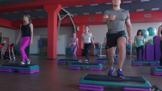 Full length of people performing step aerobics exercise in gym