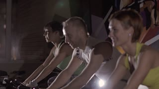 Group of sport people at fitness club exercising on stationary bikes