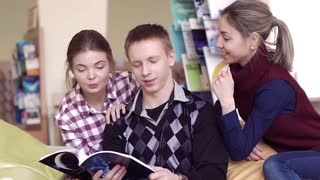 Group of three happy students in library