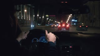 Hands on the wheel. The driver driving a black car at night.