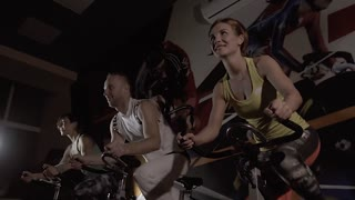 Handsome man and two young women riding stationary bikes together