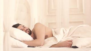 Handsome young men sleeping in white bedroom