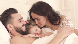 Happy family in bed waking up cute little daughter