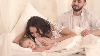 Happy family lying in bed together and waking up