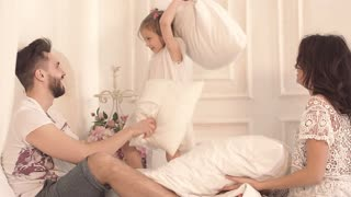 Happy family of three: mother, father and daughter having a pillow fight in bed