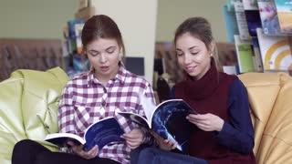 Happy university girls enjoying reading in library