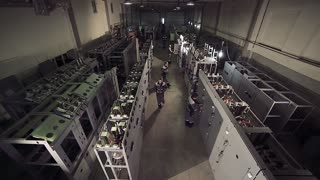 High-angle shot of factory workers working with electric meters.