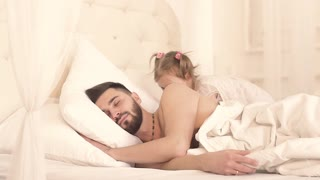 Little girl waking her father up with a kiss on cheek