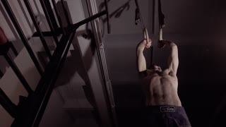 Low-angle shot of strong man working out pull ups on rings.