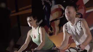Portrait of fitness people training on stationary bikes against colorful background