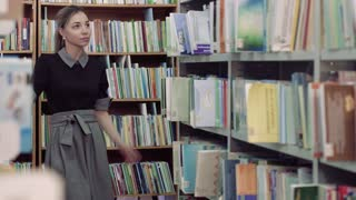 Portrait of pretty female student in library looking for a book