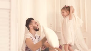Portrait of smiling and laughing father and his daughter having fun fighting with pillows