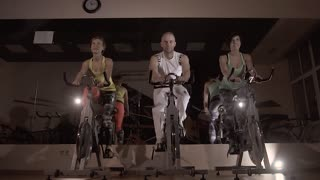 Portrait of three fitness people training on stationary bikes together at night
