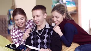 Portrait of three friendly students discussing the book in library