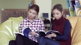 Portrait of two focused college girls reading scientific magazines