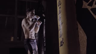 Portrait of young boxer punching the boxing bag.