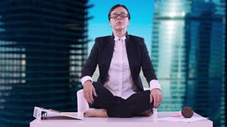 Portrait of young business woman in the office. She sat on the Desk in the Lotus position and meditating in a business suit. Brunette with glasses and eyes closed, takes a deep breath and exhale.