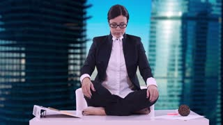 Portrait of young business woman in the office. She sat on the Desk in the Lotus position and meditating in a business suit. Brunette with glasses opens her eyes and smiles.