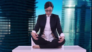 Portrait of young business woman in the office. She sat on the Desk in the Lotus position and meditating in a business suit. In the background of the business center