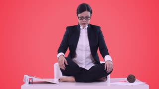Portrait of young business woman in the office. She sat on the Desk in the Lotus position and meditating in a business suit. Red background.