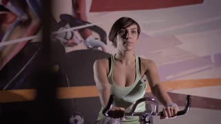 Portrait of young woman doing sport on stationary bike