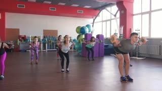 Quats with weights on training. Group of young women and man in aerobics class making exercises. Girls with barbells. Healthy lifestyle in fitness center.