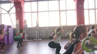 Six pretty girls and men workout in the gym.