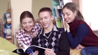 Smiling university students in library reading a book together