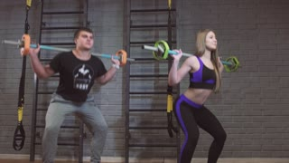 Sport, fitness, lifestyle and people concept - man and woman with barbell exercising in gym