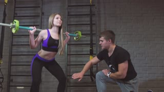 Sport, fitness, teamwork, bodybuilding and people. Young woman and personal trainer with barbell flexing muscles in gym