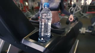 Sports woman drinks water on a treadmill in the fitness center