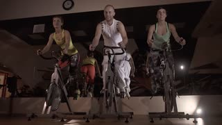 Sporty group of three: two women and a man working out on stationary bikes together
