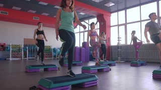 Step aerobics exercise class - group of people exercising on steppers with the trainer.