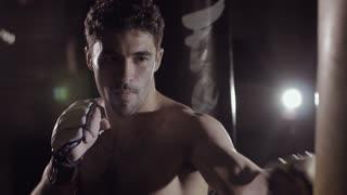 Strong caucasian man beats the boxing bag.