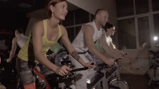 Three fitness people working out on exercise bicycles together synchronously