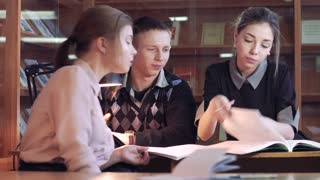 Three young students preparing research together in library