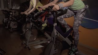 Two active sporty women enjoying their working out on stationary bicycles together