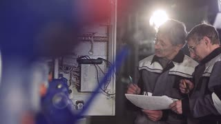 Two factory electricians discussing electric meter.