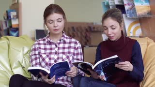 Two friendly female students in reading room browsing through magazines