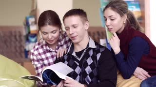 Two girls and a boy studying the book together
